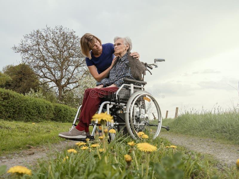 Комфорты попечителя потревожились старшая женщина с кресло-коляской стоковая фотография