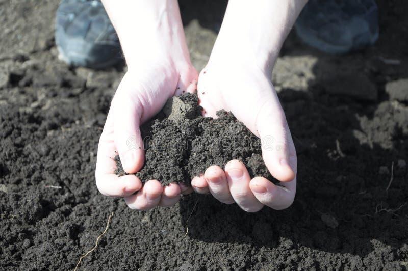 Ком земли в руках фермера стоковая фотография rf