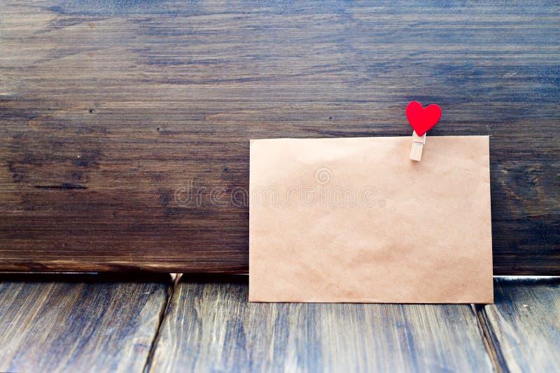 Конверт зажима Kraft бумажного в форме сердца на деревянной предпосылке, дне ` s валентинки, ориентациях ` s людей стоковая фотография