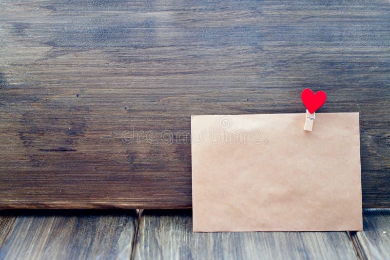 Конверт зажима Kraft бумажного в форме сердца на деревянной предпосылке, дне ` s валентинки, ориентациях ` s людей стоковые изображения