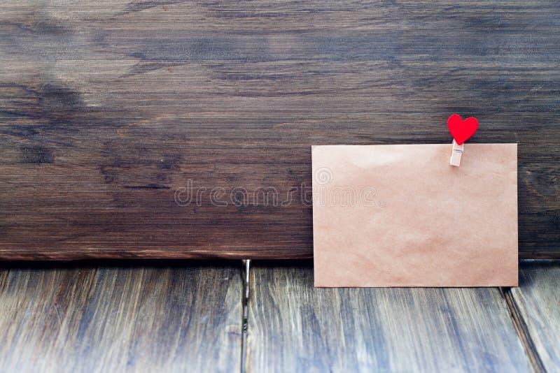 Конверт зажима Kraft бумажного в форме сердца на деревянной предпосылке, дне ` s валентинки, ориентациях ` s людей стоковые фотографии rf