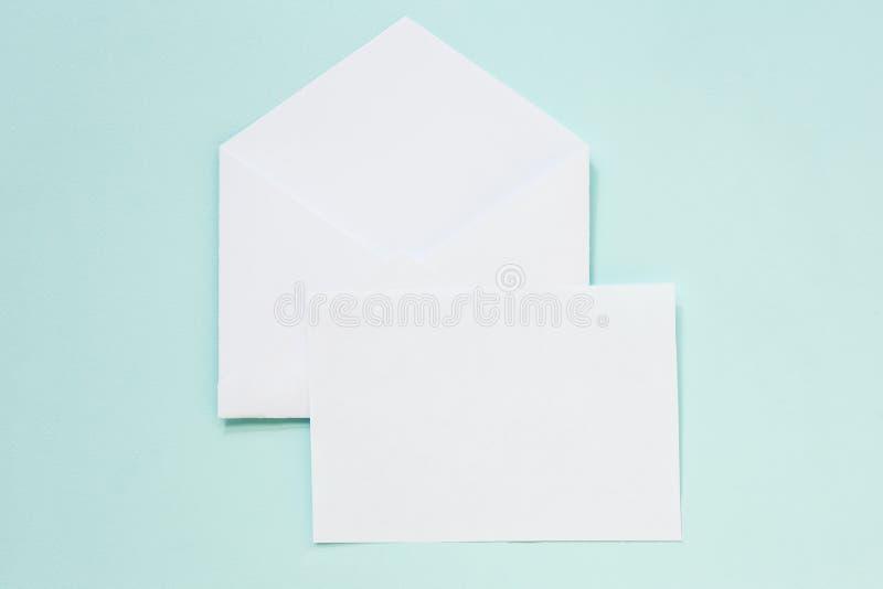 Конверт и чистый лист бумаги на пастельной голубой предпосылке насмешка вверх, взгляд сверху стоковое фото rf