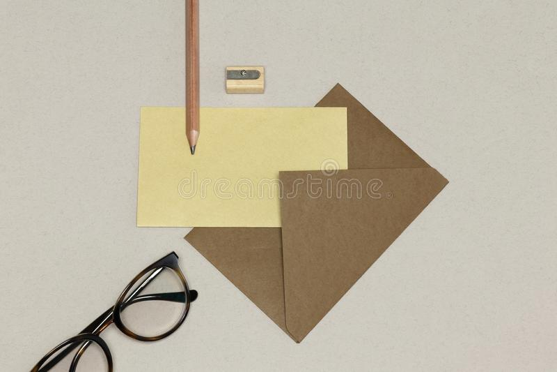 Конверт kraft, деревянный карандаш & заточник, зрелища на белой текстуре стоковое изображение