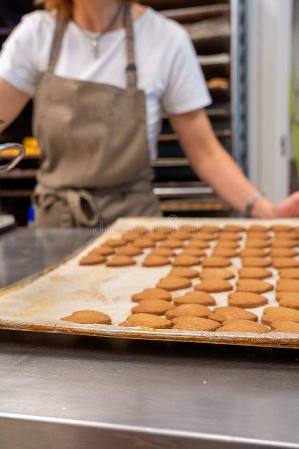 Кондитер работая, принимает вне тесто чая, печенья от подноса печи стоковое изображение rf