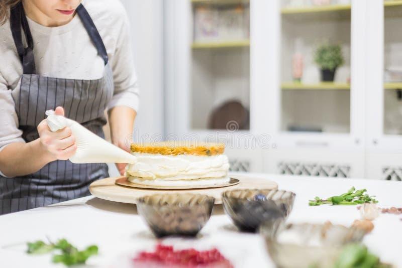 Кондитер с сумкой печенья сжимая сливк на торте на кухне r стоковая фотография