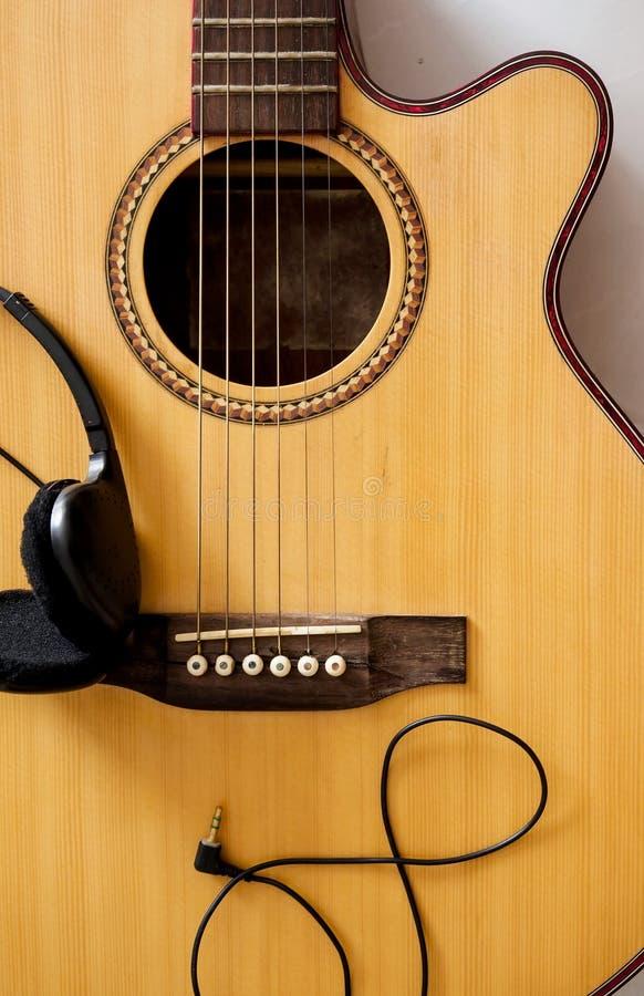Конец акустической гитары поднимающий вверх и наушники стоковые изображения