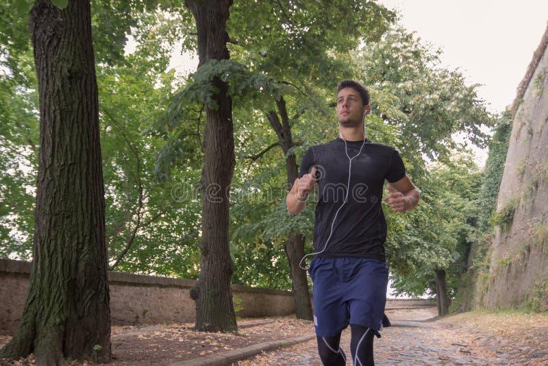 Конец бегуна jogger спортсмена молодого человека вверх outdoors стоковое изображение