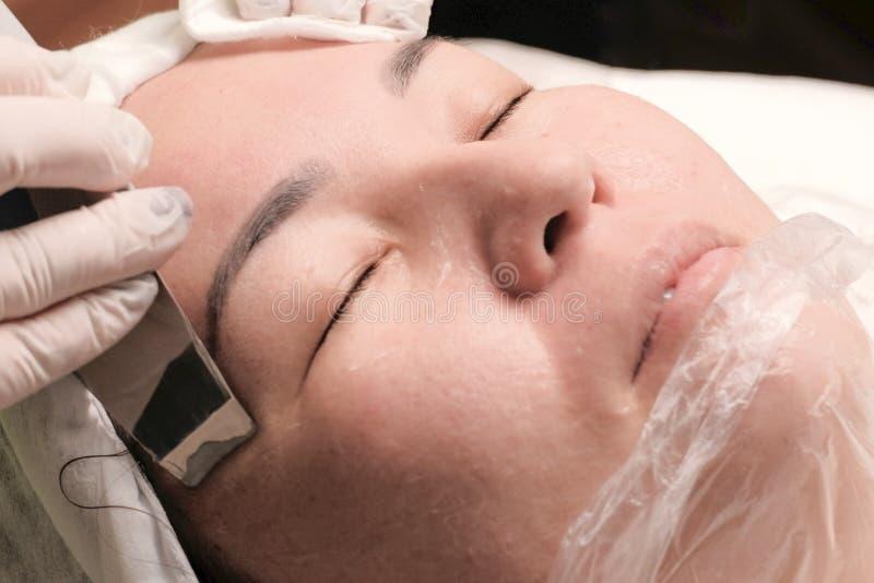 конец вверх Азиатская средн-достигшая возраста женщина лежит в медицинском офисе салона красоты Косметическая процедура для очища стоковое изображение