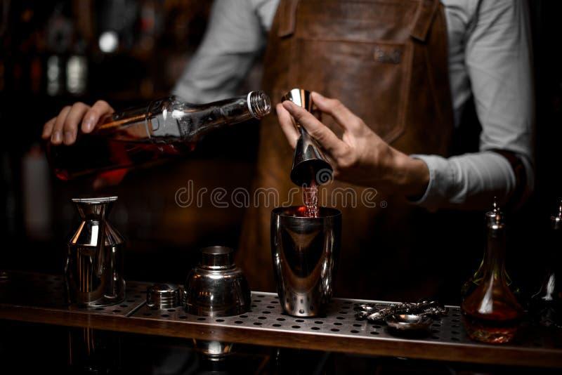 Конец-вверх алкоголя бармена лить от джиггера к шейкеру стоковая фотография rf