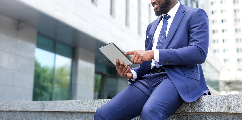 Конец-вверх африканского бизнесмена используя цифровой планшет пока сидящ предпосылки офиса стоковое изображение rf