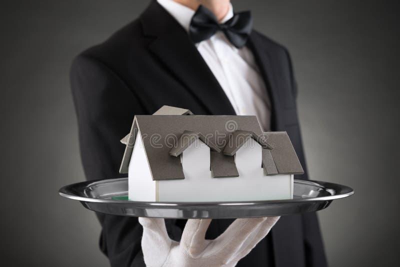 Конец-вверх Батлера с моделью дома стоковые фото