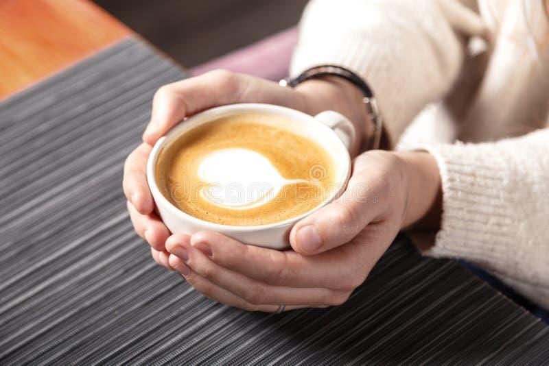 Конец-вверх белой чашки горячего кофе искусства latte с формой сердца в руках маленькой девочки Релаксация, кружка кофе стоковое изображение
