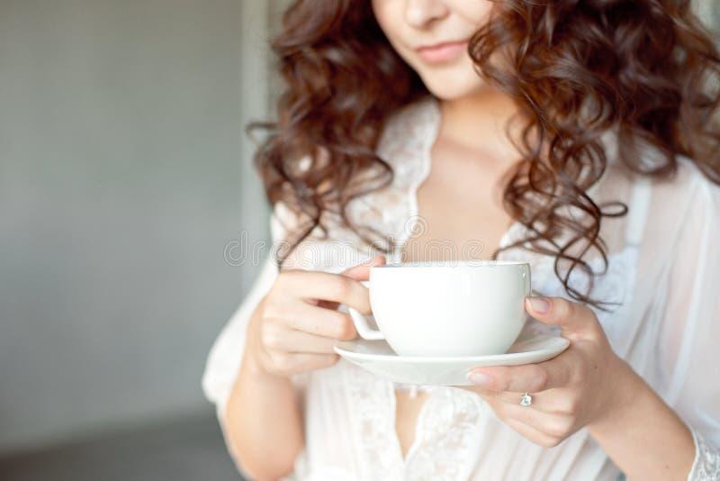 Конец-вверх белой чашки горячего кофе искусства latte с формой сердца в руках маленькой девочки стоковая фотография