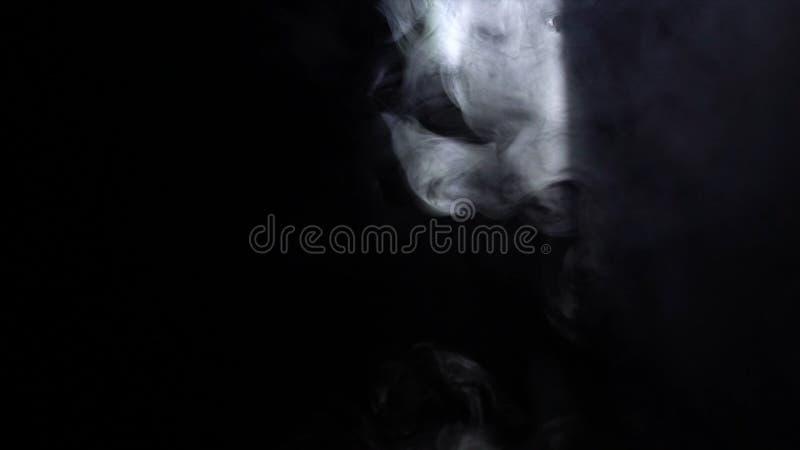 Конец-вверх белых слоек дыма завихряясь в луче света в темной комнате E Дым в темноте стоковые фото