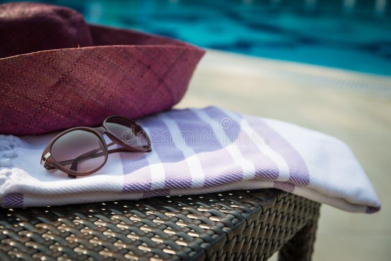Конец-вверх белых и фиолетовых турецкого полотенца, солнечных очков и соломенной шляпы на lounger ротанга с голубым бассейном как стоковая фотография