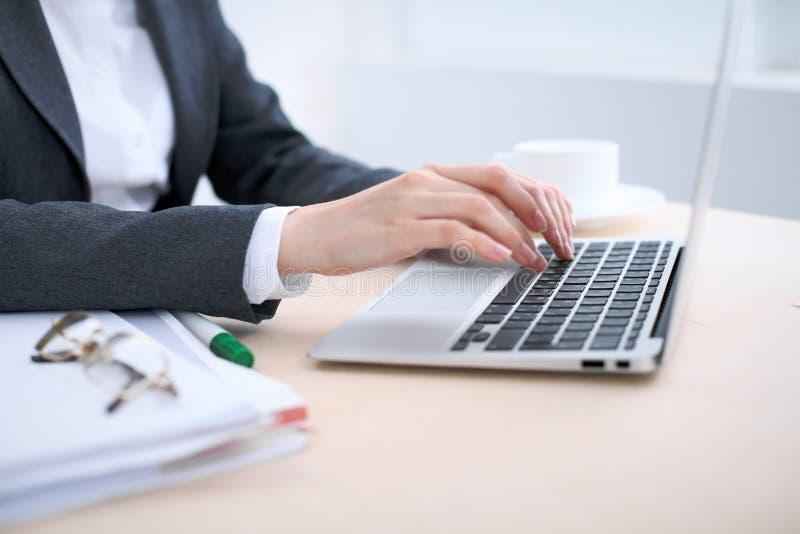 Конец-вверх бизнес-леди вручает печатать на портативном компьютере в офисе покрашенном белизной стоковое фото