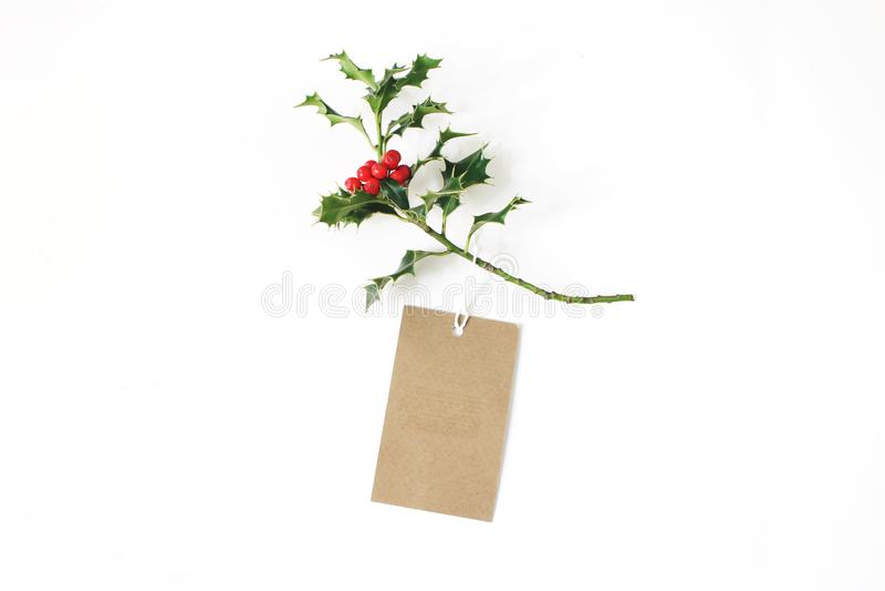 Конец-вверх бирки подарка бумаги ремесла с веревочкой и зеленой ветви падуба с красными ягодами изолированными на белой предпосыл стоковые фотографии rf