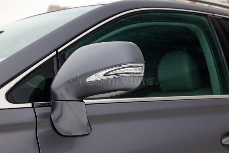 Конец-вверх бортового зеркала тела автомобиля с элементами хрома в дизайне асфальта серого цвета седана влажного на улице, стоковое фото