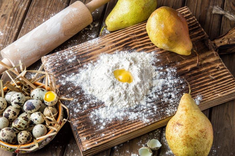 конец вверх Варить торт пасхи Желтый яичный желток в холме белой муки, окруженном зрелыми большими грушами и шаром яя жемчуга стоковая фотография rf