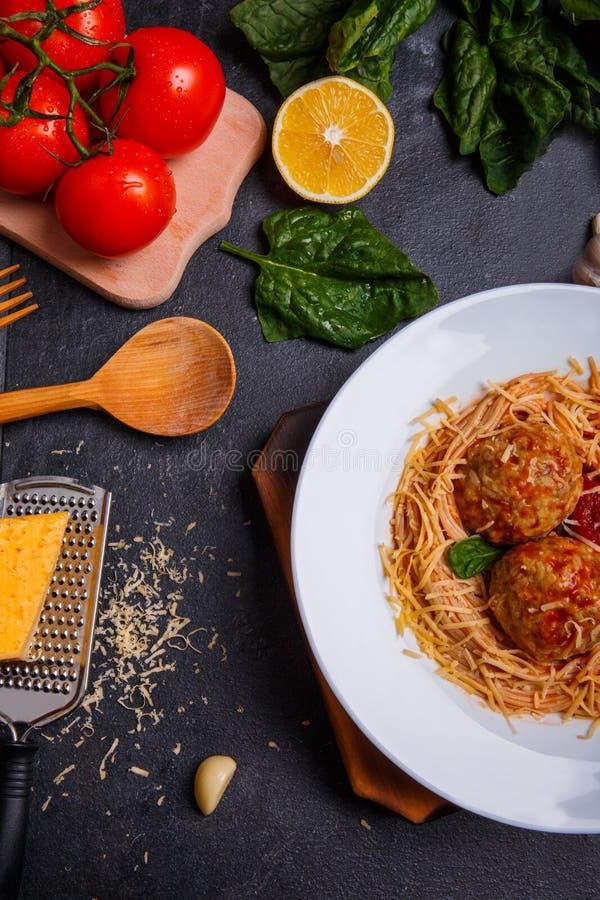 Конец-вверх, взгляд сверху, спагетти с заскрежетанным сыром и фрикадельки на плите, деревянный стол стоковые изображения