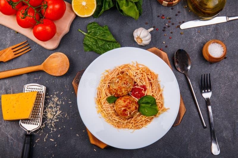 Конец-вверх, взгляд сверху, спагетти с заскрежетанным сыром и фрикадельки на плите, деревянный стол стоковые фото