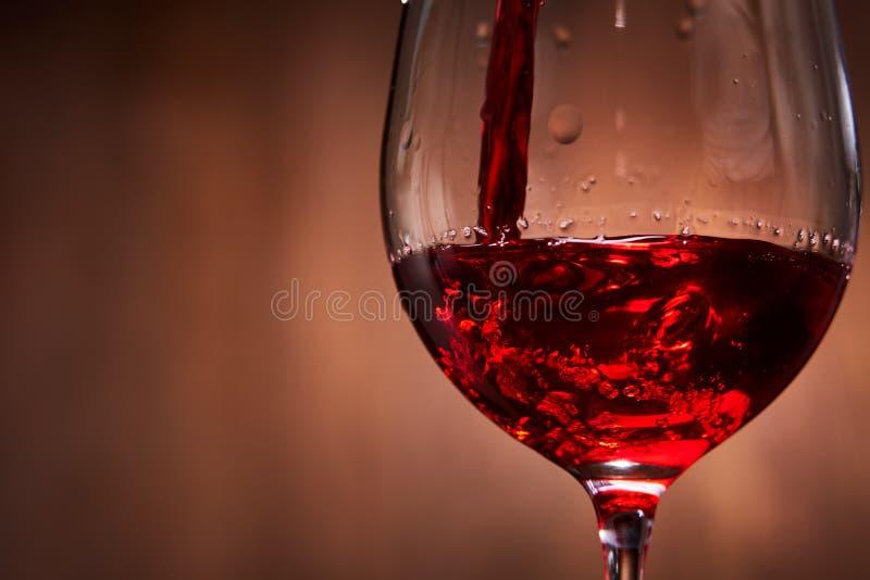 Конец-вверх вкусного красного вина лить в чисто хрупкой рюмке стоя против деревянной предпосылки стоковое изображение rf