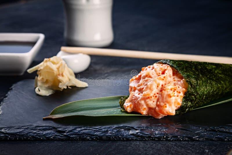 Конец-вверх вкусных суш крена руки с семгами и икрой Tobico служил на темной каменной плите с соевым соусом и имбирем r стоковое изображение