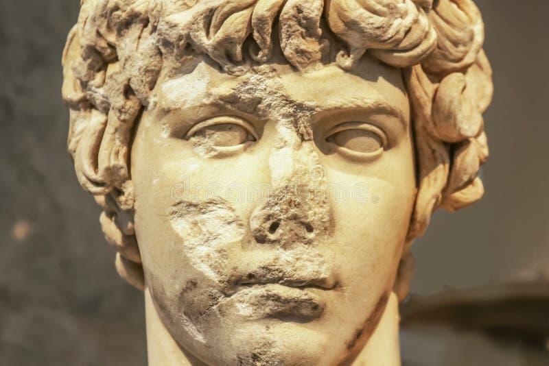 Конец-вверх головы старой мраморной статуи привлекательной греческой молодости с разрушенными частями стороны откалыванными и стоковые изображения