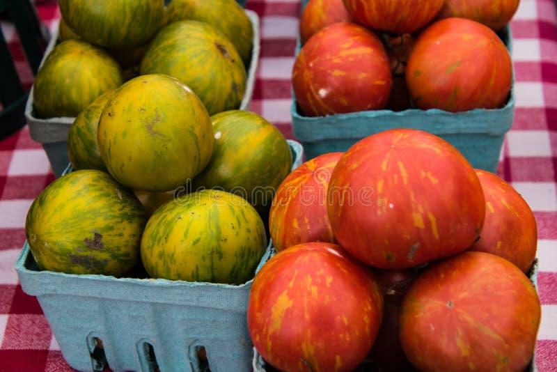 Конец-вверх голубых контейнеров кварты больших красных и зеленых томатов на белой и красной checkered скатерти стоковое изображение