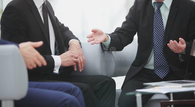 конец вверх группа в составе бизнесмены говоря на встрече стоковое фото