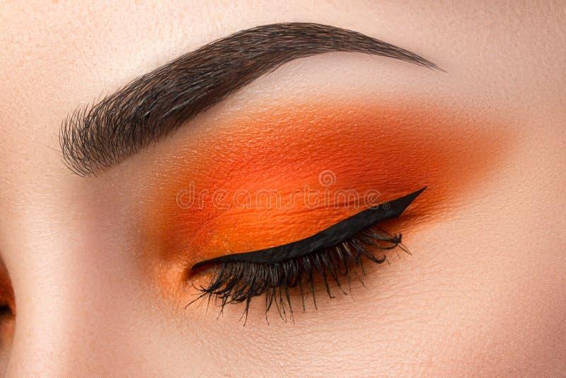 Конец-вверх глаза женщины с красивым оранжевым smokey наблюдает с bla стоковые фото