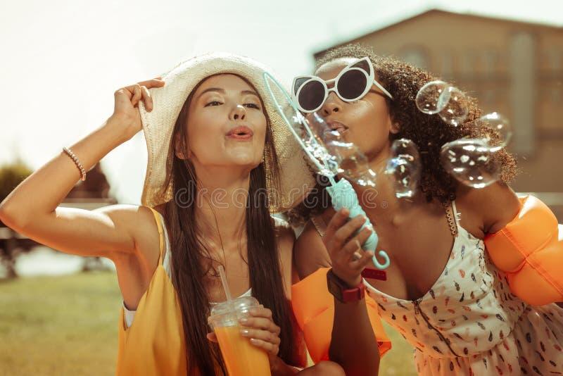 Конец-вверх дам молод-взрослого принимаясь за дующ пузыри стоковое фото rf