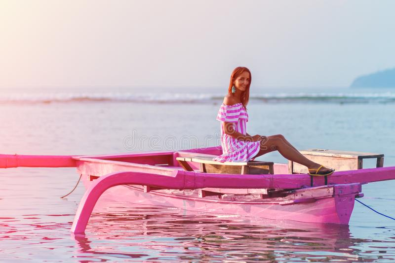 Конец-вверх девушки на маленькой лодке причаленной на подкрашиванном заходе солнца, стоковое фото rf