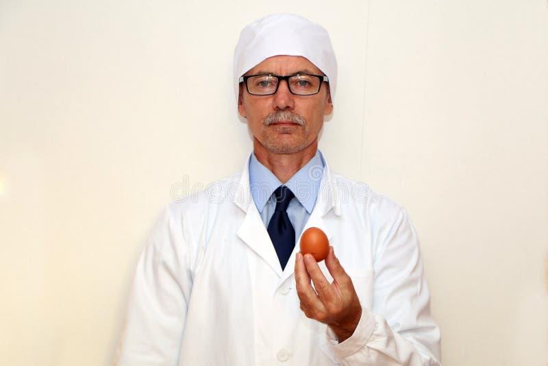 Конец-вверх - доктор держит яйцо диеты в его руках стоковое фото rf