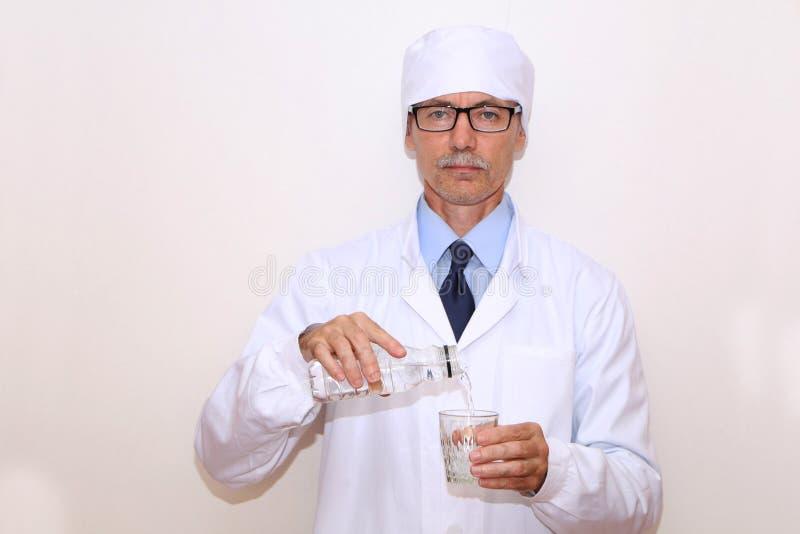 Конец-вверх - доктор льет минеральную воду в стекло стоковые изображения