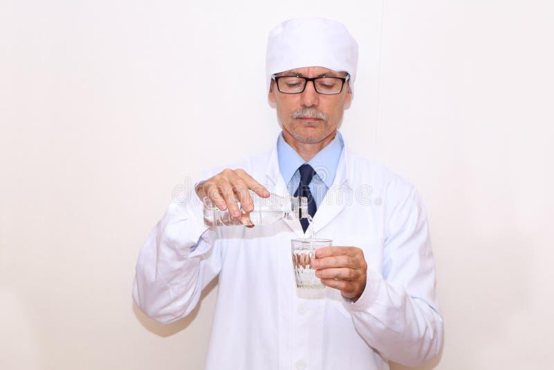 Конец-вверх - доктор льет минеральную воду в стекло стоковое изображение