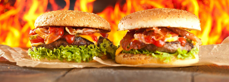 Конец-вверх домашних сделанных бургеров с огнем пылает стоковые изображения