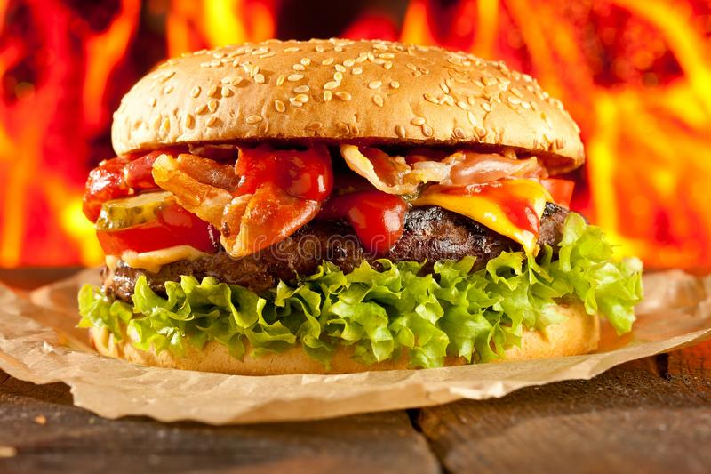 Конец-вверх домашних сделанных бургеров с огнем пылает стоковое фото