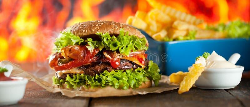 Конец-вверх домашних сделанных бургеров с огнем пылает стоковая фотография rf