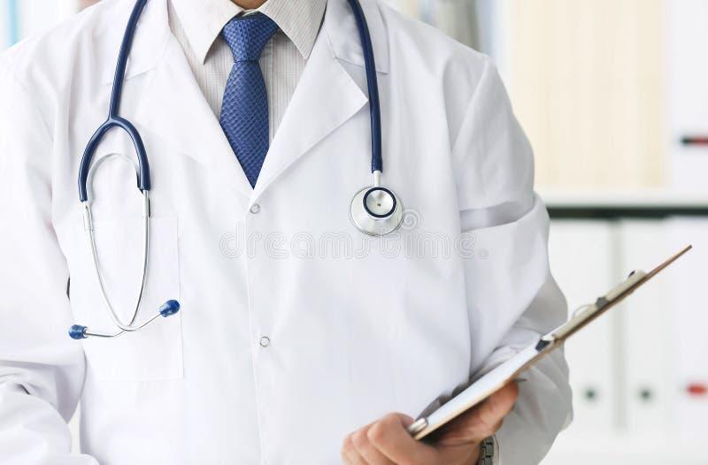 Конец-вверх доски сзажимом для бумаги с чистым листом бумаги в руке врача Мужской доктор слушает пациента держа доску сзажимом дл стоковое фото rf
