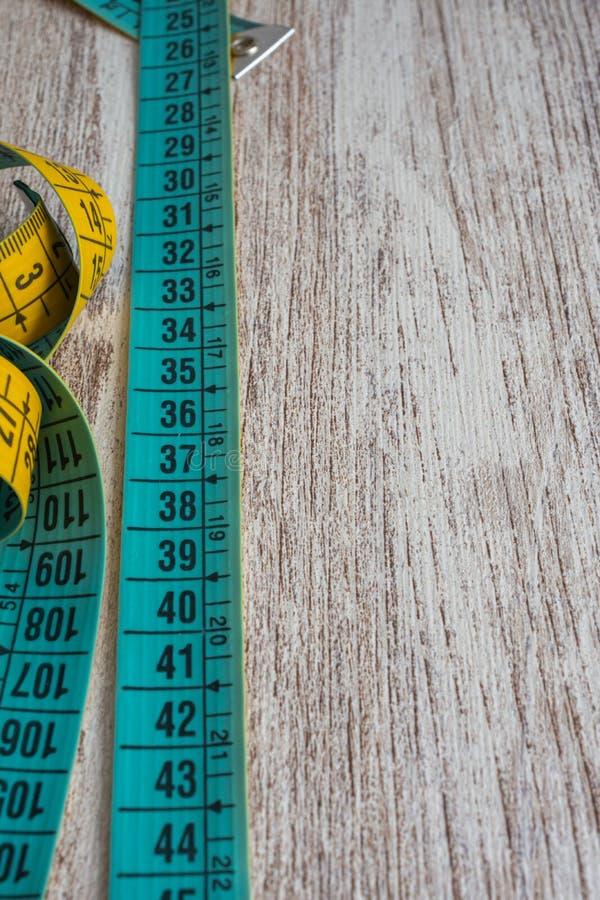 Конец-вверх желтой и голубой метрической ленты на деревянной предпосылке стоковая фотография