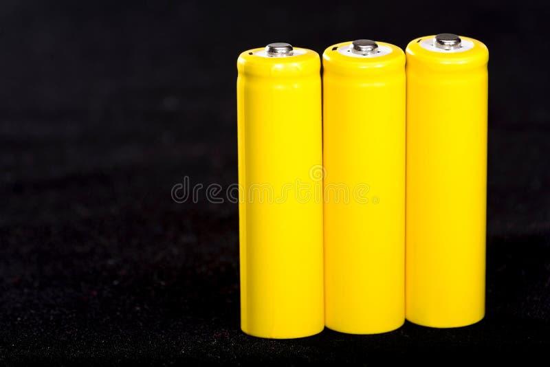 Конец-вверх 3 желтый батарей на темной черноте запачкал предпосылку electrics Сила батареи Аккумулятор на ткани с vill стоковые фото