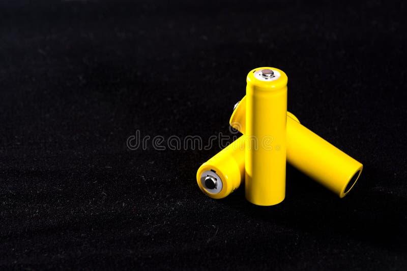 Конец-вверх 3 желтый батарей на темной черноте запачкал предпосылку electrics Сила батареи Аккумулятор на ткани с vill стоковые изображения