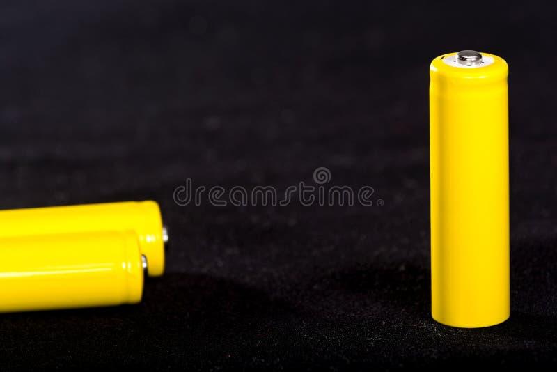 Конец-вверх 3 желтый батарей на темной черноте запачкал предпосылку electrics Сила батареи Аккумулятор на ткани с vill стоковое фото rf