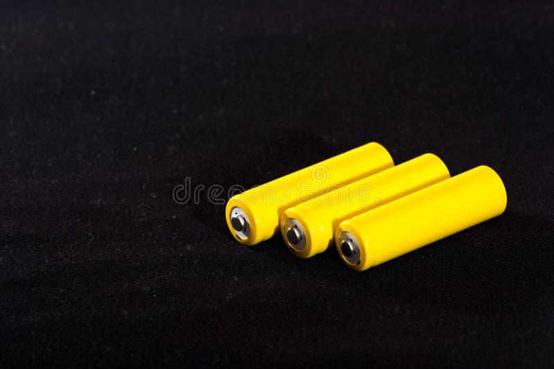 Конец-вверх 3 желтый батарей на темной черноте запачкал предпосылку electrics Сила батареи Аккумулятор на ткани с vill стоковые фотографии rf
