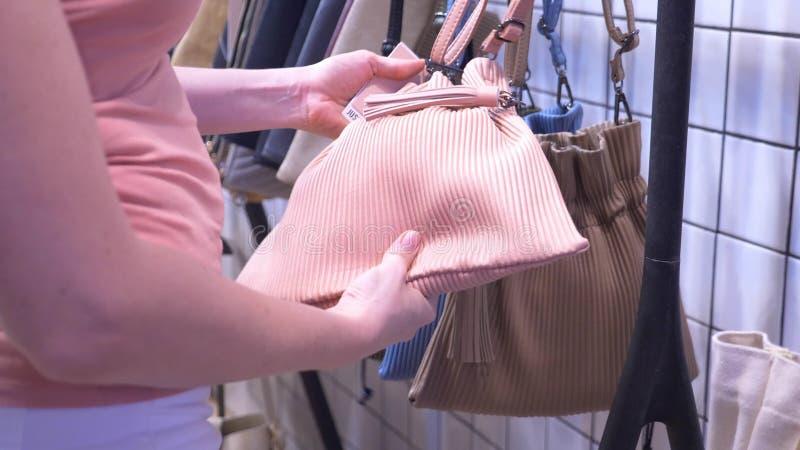Конец-вверх, женские руки девушка выбирает сумку в торговом центре стоковое изображение rf