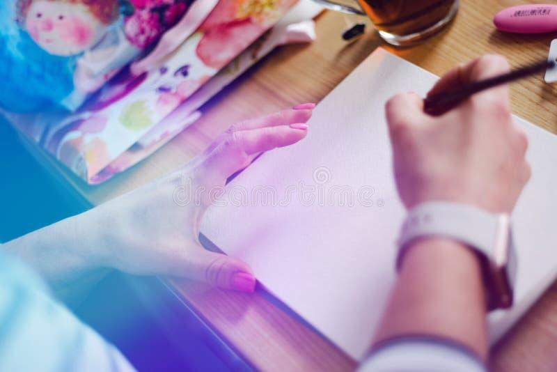 Конец-вверх женских рук делая примечания в блокноте на офисе, светлый тонизировать стоковые фото