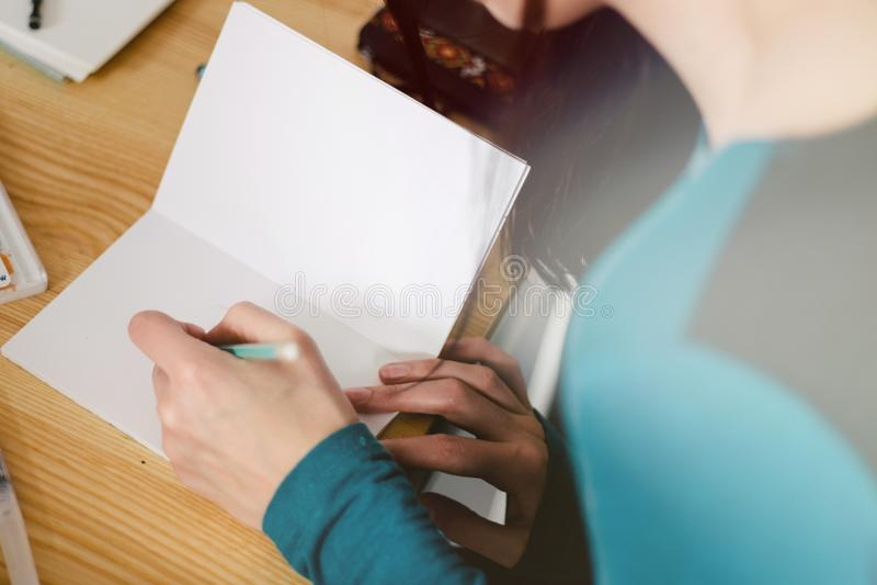 Конец-вверх женских рук делая примечания в блокноте на офисе, светлый тонизировать стоковое фото rf