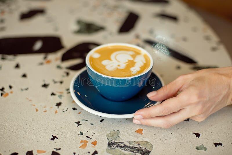Конец-вверх женских рук держа сотовый телефон, девушку сидит в видео кофе уютного кафа выпивая наблюдая на черни стоковое фото rf