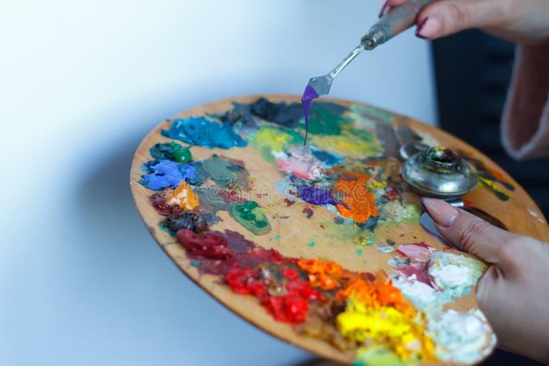 Конец-вверх женских рук смешивая краски на палитре со шпателем против белого холста, создавая картину маслом стоковое изображение
